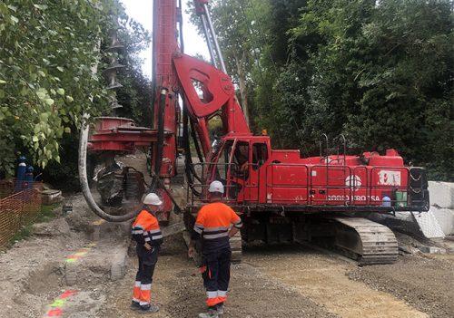 Dos trabajadores de Rodio Kronsa al costado de una máquina pilotadora.